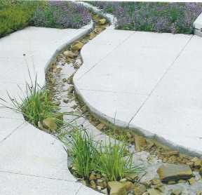 патио пересекает рукотворный ручей с каменным дном и водными растениями.